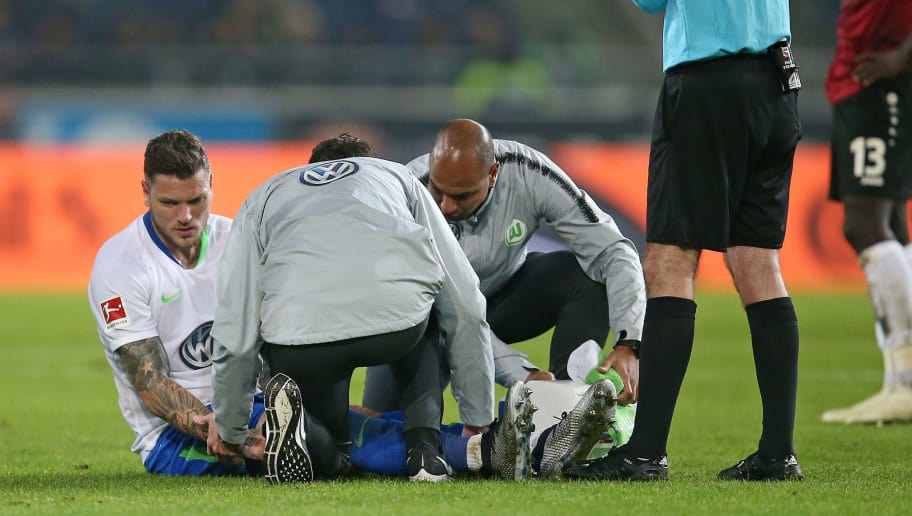 HANOVER, GERMANY - NOVEMBER 09: Daniel Ginczek (L) of VfL Wolfsburg sits on the ground and need medical aid , Referee Marco Fritz (R) next to him during the Bundesliga match between Hannover 96 and VfL Wolfsburg at HDI-Arena on November 9, 2018 in Hanover, Germany. (Photo by Cathrin Mueller/Bongarts/Getty Images)
