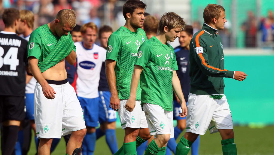 HEIDENHEIM, GERMANY - JULY 30: (L-R) Andreas Wolf, Mehmet Ekici, Marko Marin and Florian Trinks of Bremen look dejected after losing 1-2 the first round DFB Cup match between 1. FC Heidenheim and Werder Bremen at Voith-Arena on July 30, 2011 in Heidenheim, Germany.  (Photo by Christof Koepsel/Bongarts/Getty Images)