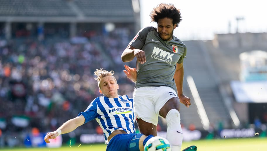 BERLIN, GERMANY - APRIL 28: Caiuby Francisco da Silva of FC Augsburg is tackled by Peter Pekarik of Hertha BSC during the Bundesliga match between Hertha BSC and FC Augsburg at Olympiastadion on April 28, 2018 in Berlin, Germany. (Photo by Boris Streubel/Bongarts/Getty Images)