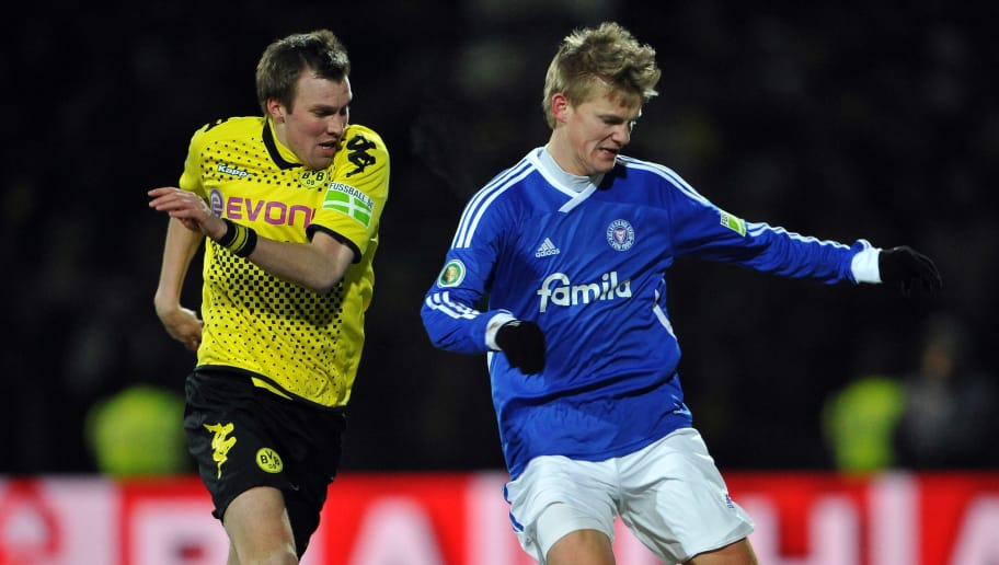 KIEL, GERMANY - FEBRUARY 07:  Kevin Grosskreutz of Dortmund challenges for the ball with Dan-Patrick Poggenberg of Kiel during the DFB Cup Quarter Final match between Holstein Kiel and Borussia Dortmund at Holstein-Stadion on February 7, 2012 in Kiel, Germany.  (Photo by Stuart Franklin/Bongarts/Getty Images)