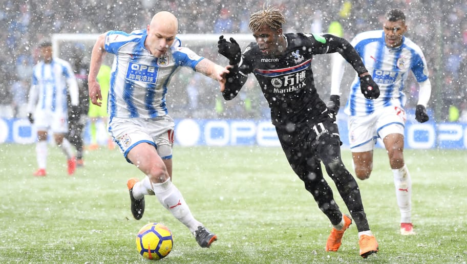 HUDDERSFIELD, ENGLAND - MARCH 17: Wilfried Zaha of Crystal Palace is challenged by Aaron Mooy of Huddersfield Town during the Premier League match between Huddersfield Town and Crystal Palace at John Smith's Stadium on March 17, 2018 in Huddersfield, England.  (Photo by Gareth Copley/Getty Images)