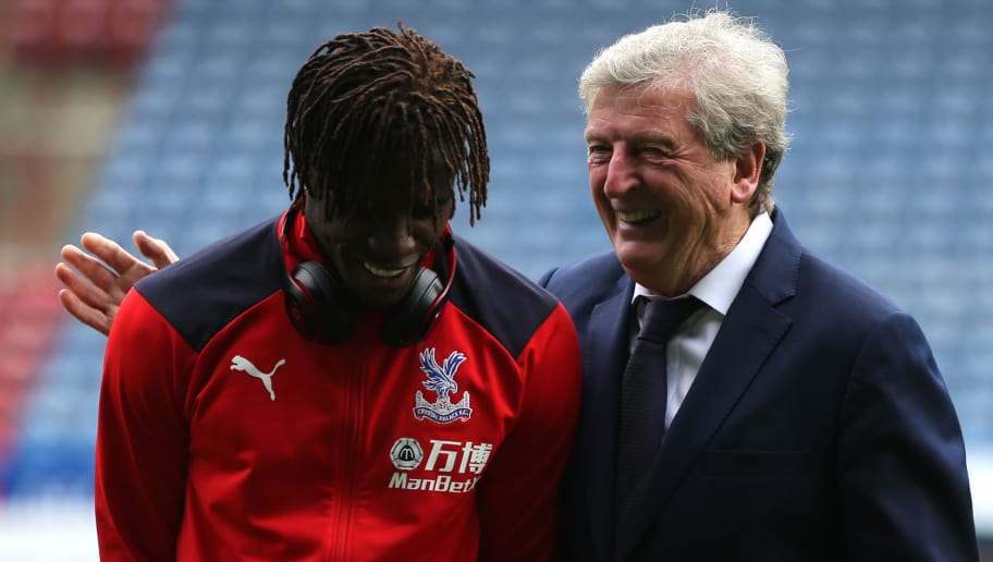 HUDDERSFIELD, ENGLAND - SEPTEMBER 15:  Wilfried Zaha of Crystal Palace (L) and Roy Hodgson, Manager of Crystal Palace speak ahead of the Premier League match between Huddersfield Town and Crystal Palace at John Smith's Stadium on September 15, 2018 in Huddersfield, United Kingdom.  (Photo by Nigel Roddis/Getty Images)