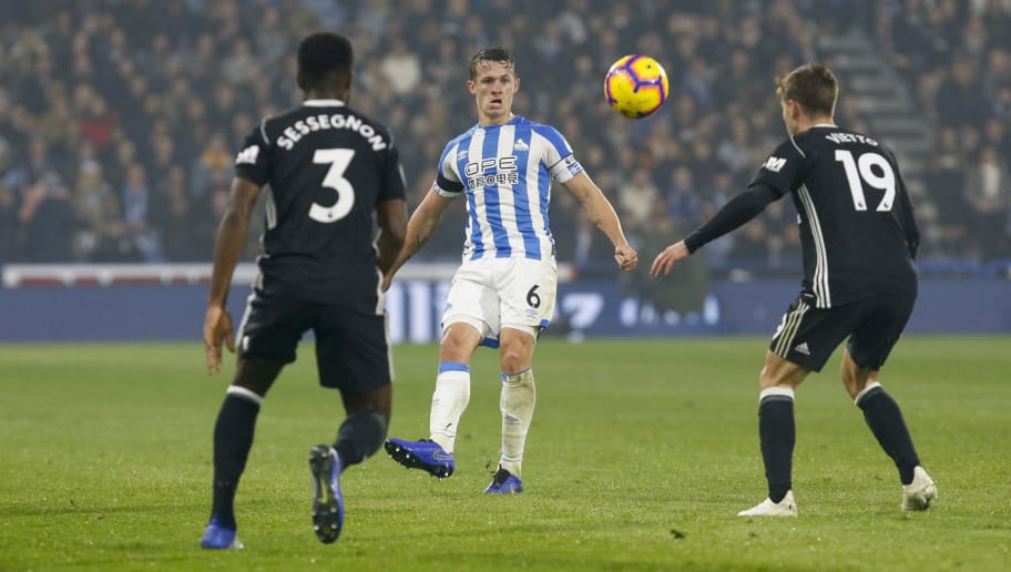 HUDDERSFIELD, ENGLAND - NOVEMBER 05:  Jonathan Hogg of Huddersfield Town chips the ball past Ryan Sessegnon of Fulham FC Luciano Vietto of Fulham FC during the Premier League match between Huddersfield Town and Fulham FC at John Smith's Stadium on November 5, 2018 in Huddersfield, United Kingdom. (Photo by John Early/Getty Images)