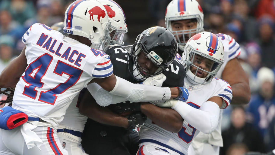 BUFFALO, NY - NOVEMBER 25: Leonard Fournette #27 of the Jacksonville Jaguars is tackled by Micah Hyde #23 of the Buffalo Bills and Levi Wallace #47 as he runs with the ball in the third quarter during NFL game action at New Era Field on November 25, 2018 in Buffalo, New York. (Photo by Tom Szczerbowski/Getty Images)