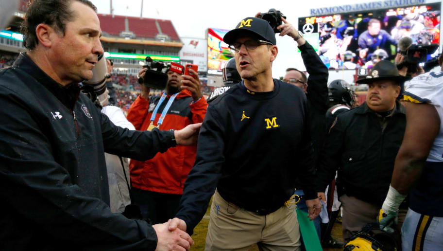 TAMPA, FL - JANUARY 1:  Head coach Will Muschamp of the South Carolina Gamecocks shakes hands on the field with head coach Jim Harbaugh of the Michigan Wolverines following the Gamecocks' 26-19 win over the  Wolverines at the Outback Bowl NCAA college football game on January 1, 2018 at Raymond James Stadium in Tampa, Florida. (Photo by Brian Blanco/Getty Images)