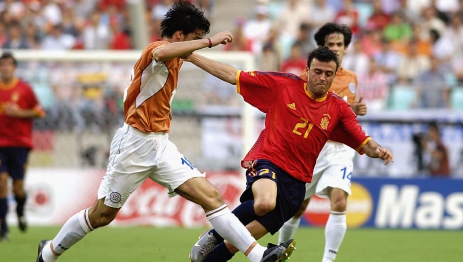 JEONJU - JUNE 7:  Julio Cesar Caceres of Paraguay tackles Luis Enrique of Spain during the FIFA World Cup Finals 2002 Group B match played at the Jeonju World Cup Stadium, in Jeonju, South Korea on June 7, 2002. Spain won the match 3-1. DIGITAL IMAGE. (Photo by Shaun Botterill/Getty Images)