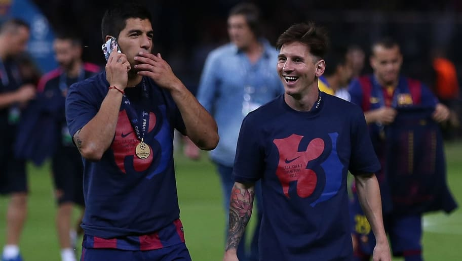 BERLIN, GERMANY - JUNE 6: Luis Suarez of FC Barcelona speaks on a mobile phone as team-mate Lionel Messi looks on following the UEFA Champions League Final match between Juventus and FC Barcelona at the Olympiastadion on June 6, 2015 in Berlin, Germany. (Photo by Chris Brunskill Ltd/Getty Images)