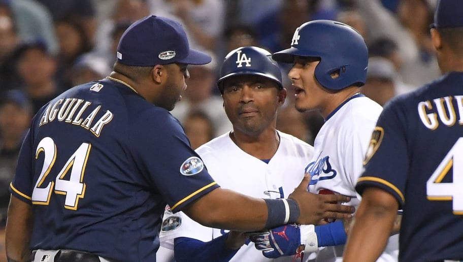 LOS ANGELES, CA - OCTOBER 16:  Manny Machado #8 of the Los Angeles Dodgers and Jesus Aguilar #24 of the Milwaukee Brewers exchange words during the tenth inning in Game Four of the National League Championship Series at Dodger Stadium on October 16, 2018 in Los Angeles, California.  (Photo by Harry How/Getty Images)