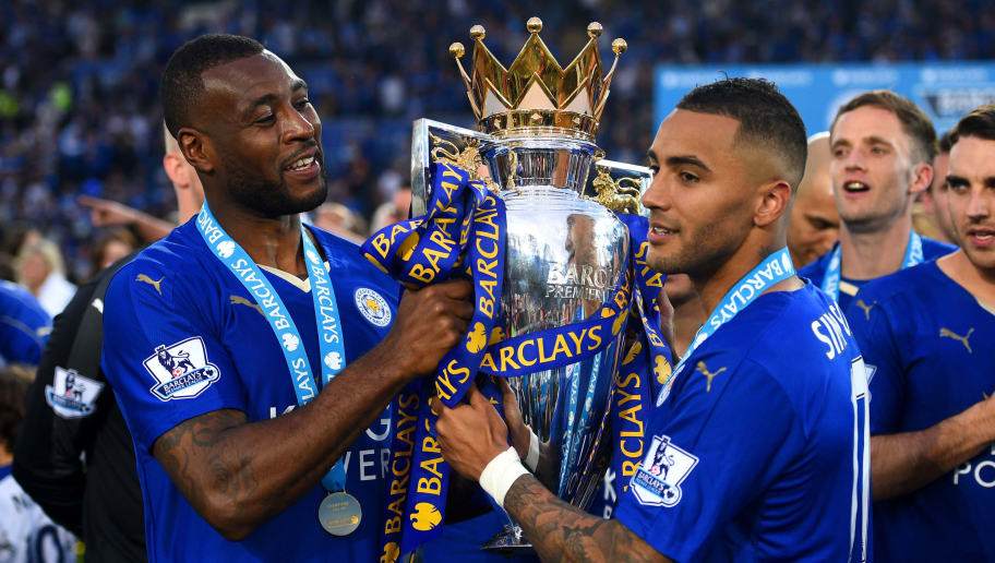 LEICESTER, ENGLAND - MAY 07:  Wes Morgan and Danny Simpson of Leicester City pose for photographs with the Premier League Trophy as players and staffs celebrate the season champions after the Barclays Premier League match between Leicester City and Everton at The King Power Stadium on May 7, 2016 in Leicester, United Kingdom.  (Photo by Shaun Botterill/Getty Images)