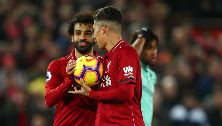LIVERPOOL, ENGLAND - DECEMBER 29:  Mohamed Salah of Liverpool passes Roberto Firmino of Liverpool the match ball to take the penalty for his hat trick during the Premier League match between Liverpool FC and Arsenal FC at Anfield on December 29, 2018 in Liverpool, United Kingdom. (Photo by Robbie Jay Barratt - AMA/Getty Images)