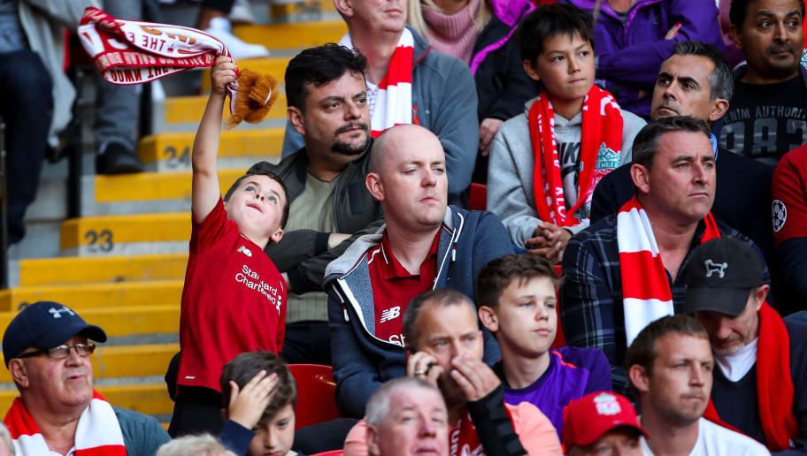 LIVERPOOL, ENGLAND - AUGUST 25: A young fan of Liverpool waves a scarf  during the Premier League match between Liverpool FC and Brighton & Hove Albion at Anfield on August 25, 2018 in Liverpool, United Kingdom. (Photo by Robbie Jay Barratt - AMA/Getty Images)