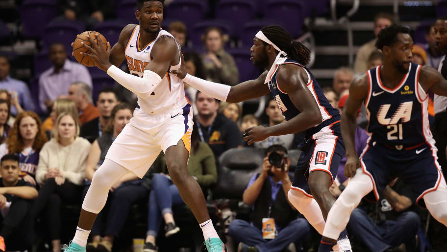 PHOENIX, ARIZONA - DECEMBER 10: Deandre Ayton #22 of the Phoenix Suns handles the ball under pressure from Montrezl Harrell #5 of the LA Clippers during the first half of the NBA game at Talking Stick Resort Arena on December 10, 2018 in Phoenix, Arizona. NOTE TO USER: User expressly acknowledges and agrees that, by downloading and or using this photograph, User is consenting to the terms and conditions of the Getty Images License Agreement. (Photo by Christian Petersen/Getty Images)