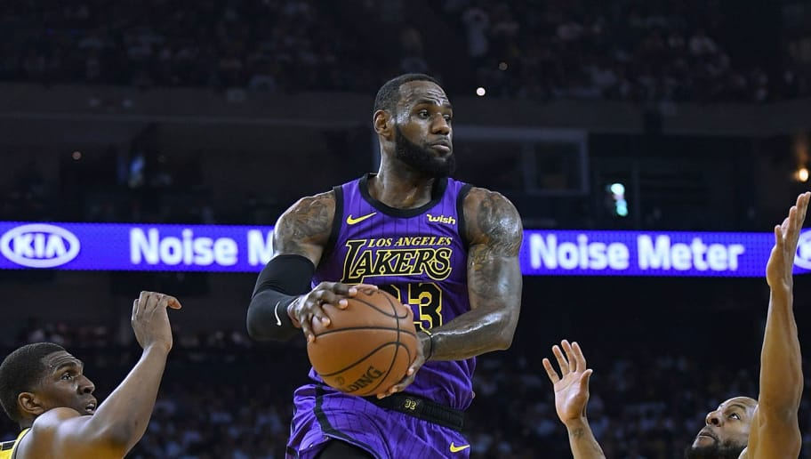OAKLAND, CA - DECEMBER 25:  LeBron James #23 of the Los Angeles Lakers leaps in the air to pass the ball between Kevon Looney #5 and Andre Iguodala #9 of the Golden State Warriors during the first half of their NBA Basketball game at ORACLE Arena on December 25, 2018 in Oakland, California. NOTE TO USER: User expressly acknowledges and agrees that, by downloading and or using this photograph, User is consenting to the terms and conditions of the Getty Images License Agreement.  (Photo by Thearon W. Henderson/Getty Images)