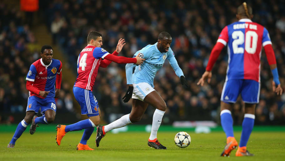 MANCHESTER, ENGLAND - MARCH 07:  Yaya Toure of Manchester City holds off a challenge from Mohamed Elyounoussi of FC Basel during the UEFA Champions League Round of 16 Second Leg match between Manchester City and FC Basel at Etihad Stadium on March 7, 2018 in Manchester, United Kingdom.  (Photo by Alex Livesey - Danehouse/Getty Images)