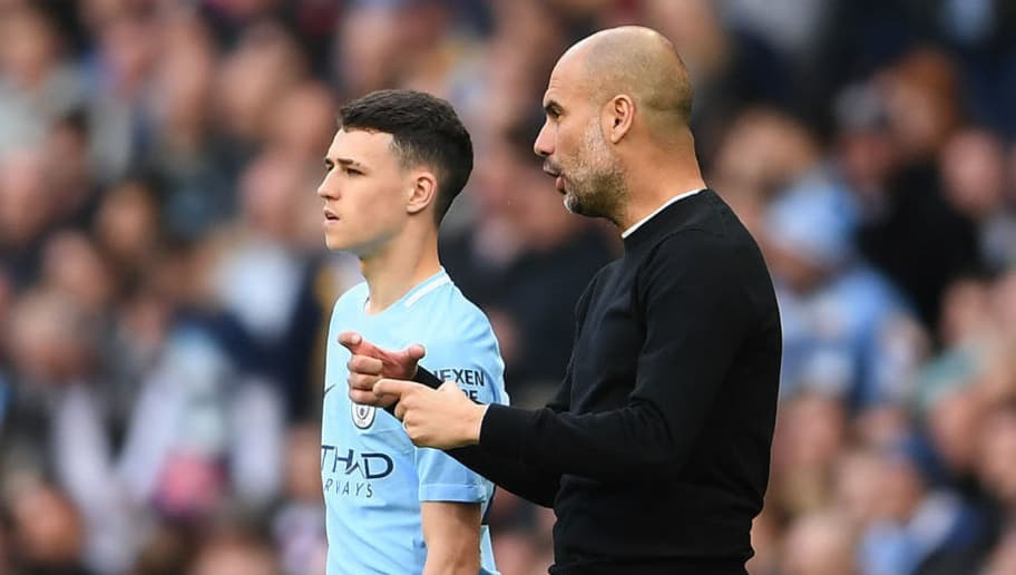 MANCHESTER, ENGLAND - APRIL 22: Phil Foden speaks with Josep Guardiola, Manager of Manchester City ahead of walking onto pitch during the Premier League match between Manchester City and Swansea City at Etihad Stadium on April 22, 2018 in Manchester, England.  (Photo by Laurence Griffiths/Getty Images)
