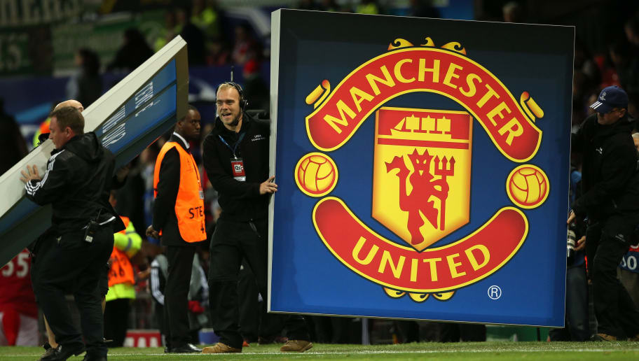 MANCHESTER, ENGLAND - SEPTEMBER 30: UEFA Champions League workers hold up a logo of Manchester United during the UEFA Champions League match between Manchester United and Wolfsburg at Old Trafford on September 30, 2015 in Manchester, United Kingdom. (Photo by Matthew Ashton - AMA/Getty Images)