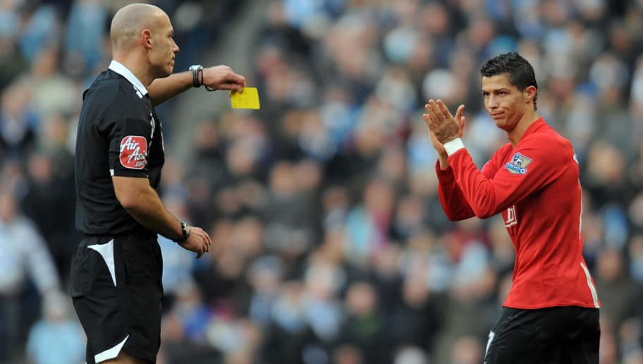 Manchester United's Portugese midfielder Cristiano Ronaldo (R) applauds the referee Howard Webb (R) as he recieves his first yellow card during the English Premier league football match against Manchester City at The City of Manchester Stadium in Manchester, north-west England on November 30, 2008. AFP PHOTO/ANDREW YATES.  FOR EDITORIAL USE ONLY Additional licence required for any commercial/promotional use or use on TV or internet (except identical online version of newspaper) of Premier League/Football League photos. Tel DataCo +44 207 2981656. Do not alter/modify photo. (Photo credit should read ANDREW YATES/AFP/Getty Images)