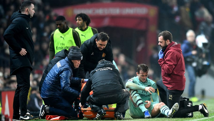 MANCHESTER, ENGLAND - DECEMBER 05:  Rob Holding of Arsenal receives medical treatment during the Premier League match between Manchester United and Arsenal FC at Old Trafford on December 5, 2018 in Manchester, United Kingdom.  (Photo by Michael Regan/Getty Images)