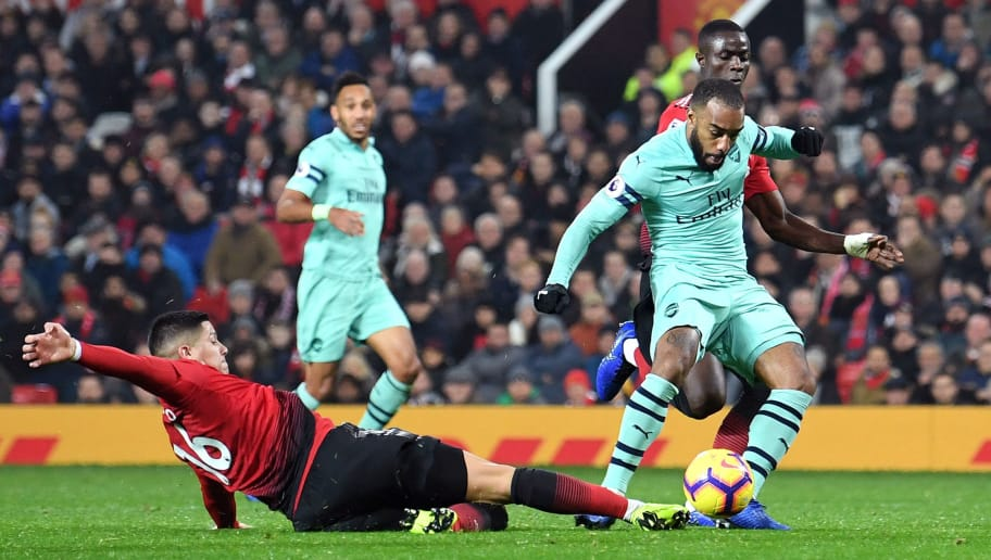MANCHESTER, ENGLAND - DECEMBER 05:  Alexandre Lacazette of Arsenal scores his team's second goal as he is challenged by Marcos Rojo of Manchester United during the Premier League match between Manchester United and Arsenal FC at Old Trafford on December 5, 2018 in Manchester, United Kingdom.  (Photo by Michael Regan/Getty Images)