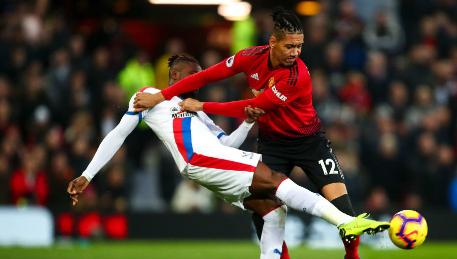 MANCHESTER, ENGLAND - NOVEMBER 24: Wilfried Zaha of Crystal Palace and Chris Smalling of Manchester United during the Premier League match between Manchester United and Crystal Palace at Old Trafford on November 24, 2018 in Manchester, United Kingdom. (Photo by Robbie Jay Barratt - AMA/Getty Images)