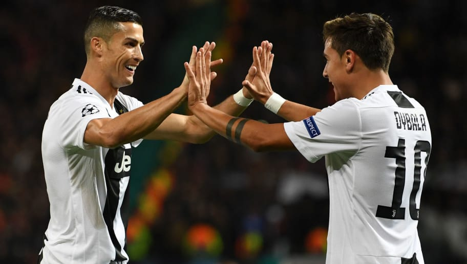 MANCHESTER, ENGLAND - OCTOBER 23:  Paulo Dybala of Juventus celebrates with teammate Cristiano Ronaldo after scoring his team's first goal during the Group H match of the UEFA Champions League between Manchester United and Juventus at Old Trafford on October 23, 2018 in Manchester, United Kingdom.  (Photo by Michael Regan/Getty Images)
