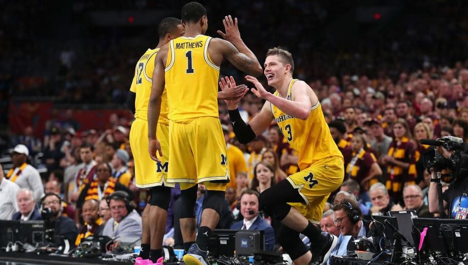 SAN ANTONIO, TX - MARCH 31: Moritz Wagner #13 of the Michigan Wolverines is helped back to the court by teammates after jumping over the scorer's table in the second half against the Loyola Ramblers during the 2018 NCAA Men's Final Four Semifinal at the Alamodome on March 31, 2018 in San Antonio, Texas.  (Photo by Tom Pennington/Getty Images)
