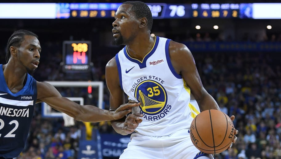 OAKLAND, CA - SEPTEMBER 29:  Kevin Durant #35 of the Golden State Warriors looks to shoot over Andrew Wiggins #22 of the Minnesota Timberwolves during an NBA basketball game at ORACLE Arena on September 29, 2018 in Oakland, California. NOTE TO USER: User expressly acknowledges and agrees that, by downloading and or using this photograph, User is consenting to the terms and conditions of the Getty Images License Agreement.  (Photo by Thearon W. Henderson/Getty Images)