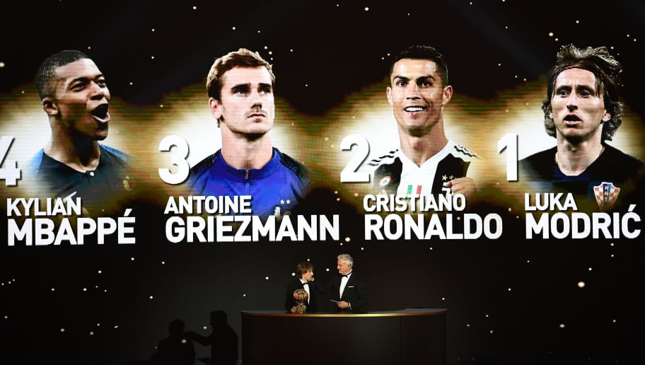 Real Madrid's Croatian midfielder Luka Modric (L) and former French footballer and host David Ginola stand under a giant screen displaying the ranking of the 4 best players of the year after receiving the 2018  Men's Ballon d'Or award for best player of the year during the 2018 Ballon d'Or award ceremony at the Grand Palais in Paris on December 3, 2018. (Photo by FRANCK FIFE / AFP)        (Photo credit should read FRANCK FIFE/AFP/Getty Images)