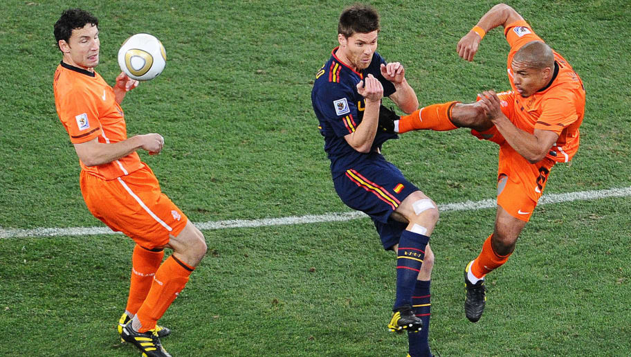 Netherlands' midfielder Nigel de Jong (R) fouls Spain's midfielder Xabi Alonso (C) with a kick to the stomach as Netherlands' midfielder Mark van Bommel (L) looks on during the 2010 World Cup football final between the Netherlands and Spain on July 11, 2010 at Soccer City stadium in Soweto, suburban Johannesburg.   NO PUSH TO MOBILE / MOBILE USE SOLELY WITHIN EDITORIAL ARTICLE    AFP PHOTO / CARL DE SOUZA (Photo credit should read CARL DE SOUZA/AFP/Getty Images)