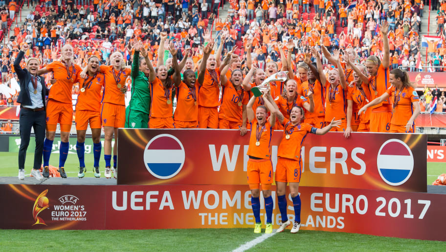 ENSCHEDE, NETHERLANDS - AUGUST 06: Mandy Van Den Berg and Sherida Spitse of Netherlands Women lift the trophy as their team mates celebrate after the UEFA Women's Euro 2017 final match between Denmark and Netherlands at De Grolsch Veste Stadium on August 6, 2017 in Enschede, Netherlands. (Photo by TF-Images/TF-Images via Getty Images)