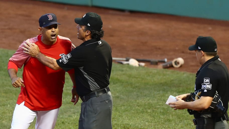 BOSTON, MA - AUGUST 03:  First base umpire Phil Cuzzi #10 holds back Alex Cora #20 of the Boston Red Sox from home plate umpire Adam Hamari #78 after being ejected in the bottom of the first inning against the New York Yankees at Fenway Park on August 3, 2018 in Boston, Massachusetts.  (Photo by Omar Rawlings/Getty Images)