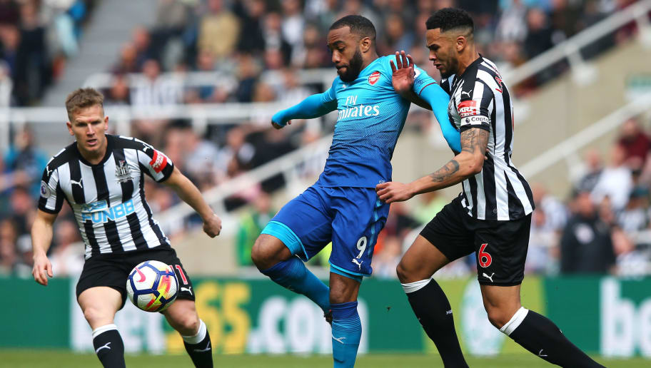 NEWCASTLE UPON TYNE, ENGLAND - APRIL 15:  Alexandre Lacazette of Arsenal, Jamaal Lascelles of Newcastle United and Matt Ritchie of Newcastle United battle for possession during the Premier League match between Newcastle United and Arsenal at St. James Park on April 15, 2018 in Newcastle upon Tyne, England.  (Photo by Alex Livesey/Getty Images)