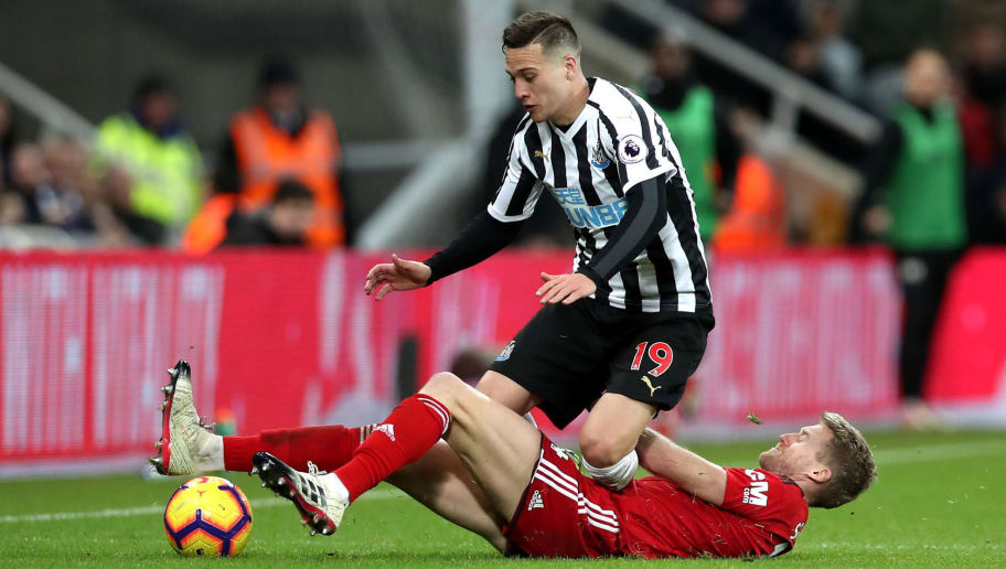 NEWCASTLE UPON TYNE, ENGLAND - DECEMBER 22:  Javier Manquillo of Newcastle United is challenged by Andre Schurrle of Fulham during the Premier League match between Newcastle United and Fulham FC at St. James Park on December 22, 2018 in Newcastle upon Tyne, United Kingdom.  (Photo by Ian MacNicol/Getty Images)