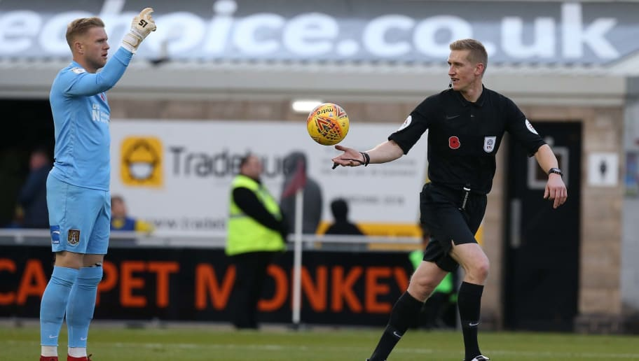 NORTHAMPTON, ENGLAND - NOVEMBER 03: Referee Scott Oldham restarts play with a drop ball as David Cornell of Northampton Town looks on during the Sky Bet League Two match between Northampton Town and Crewe Alexandra at The PTS Stadium on November 3, 2018 in Northampton, United Kingdom. (Photo by Pete Norton/Getty Images)