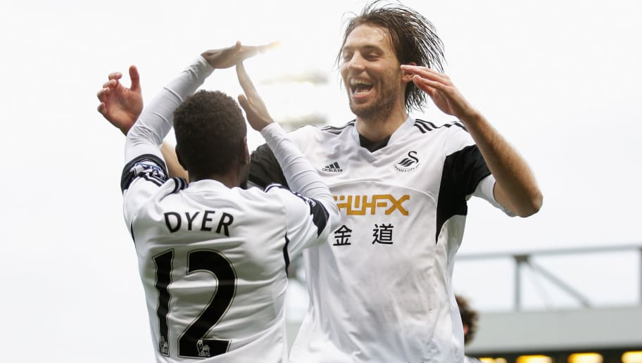 NORWICH, ENGLAND - DECEMBER 15:  Nathan Dyer of Swansea City (L) is congratulated by teammate Michu after scoring his side's first goal during the Premier League match between Norwich City and Swansea City at Carrow Road on December 15, 2013 in Norwich, England.  (Photo by Harry Engels/Getty Images)