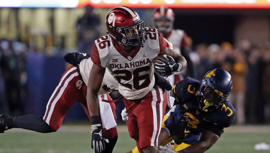 MORGANTOWN, WV - NOVEMBER 23:  Kennedy Brooks #26 of the Oklahoma Sooners rushes against Toyous Avery Jr. #3 of the West Virginia Mountaineers on November 23, 2018 at Mountaineer Field in Morgantown, West Virginia.  (Photo by Justin K. Aller/Getty Images)