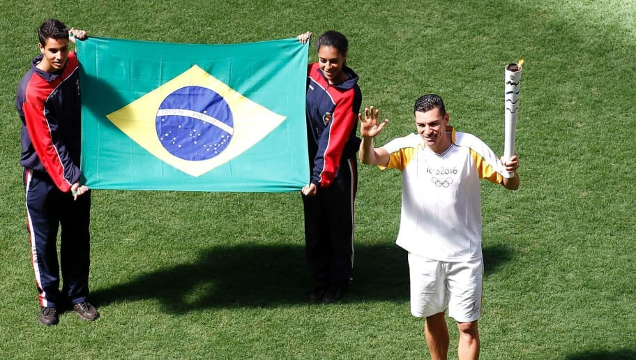 Brazilian former footballer Lucio carries the Olympic torch at the Brasilia National Stadium in Brasilia on May 3, 2016. Embattled President Dilma Rousseff greeted the Olympic flame in Brazil on Tuesday, promising not to allow a raging political crisis, which could see her suspended within days, to spoil the Rio Games. The torch will now be carried in a relay by 12,000 people through 329 cities, ending in Rio's Maracana stadium on August 5 for the opening ceremony.        / AFP / BETO BARATA        (Photo credit should read BETO BARATA/AFP/Getty Images)