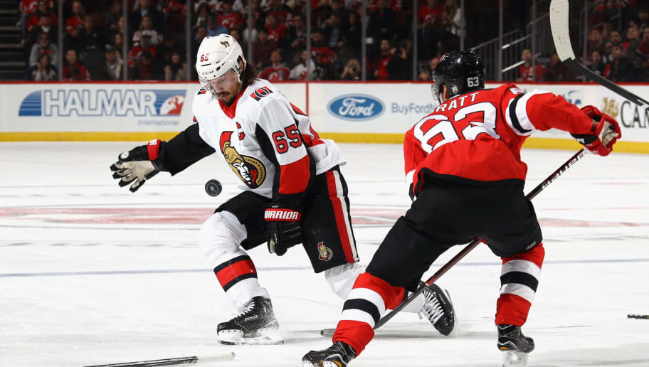 NEWARK, NJ - OCTOBER 27: Erik Karlsson #65 of the Ottawa Senators blocks the puck after breaking his stick as Jesper Bratt #63 of the New Jersey Devils looks to pick up the puck during the third period at the Prudential Center on October 27, 2017 in Newark, New Jersey.  The Devils defeated the Senators 5-4 in the shoot out. (Photo by Bruce Bennett/Getty Images)