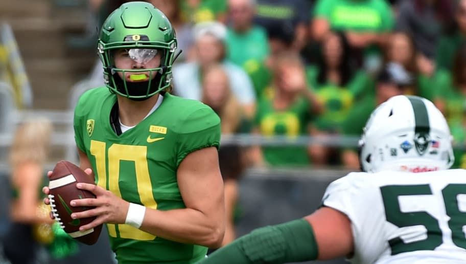 EUGENE, OR - SEPTEMBER 08: Justin Herbert #10 of the Oregon Ducks drops back to pass as defensive tackle Dallas House #58 of the Portland State Vikings apples pressure during the first half of the game against at Autzen Stadium on September 8, 2018 in Eugene, Oregon.