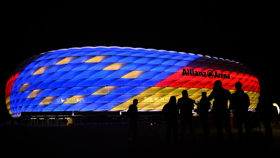 MUNICH, GERMANY - SEPTEMBER 22: People are standing in front of the Allianz Arena which is illuminated with the German Flag to show support for the German UEFA Euro 2024 application on September 22, 2018 in Munich, Germany. (Photo by Sebastian Widmann/Bongarts/Getty Images)