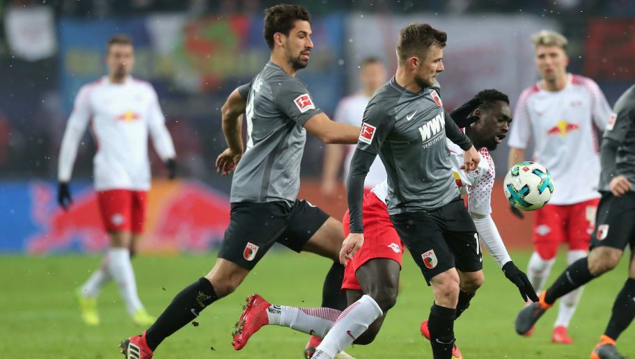 LEIPZIG, GERMANY - FEBRUARY 09:  Jean-Kevin Augustin of RB Leipzig is challenged by Daniel Baier and Rani Khedira of FC Augsburg during the Bundesliga match between RB Leipzig and FC Augsburg at Red Bull Arena on February 9, 2018 in Leipzig, Germany.  (Photo by Boris Streubel/Bongarts/Getty Images)