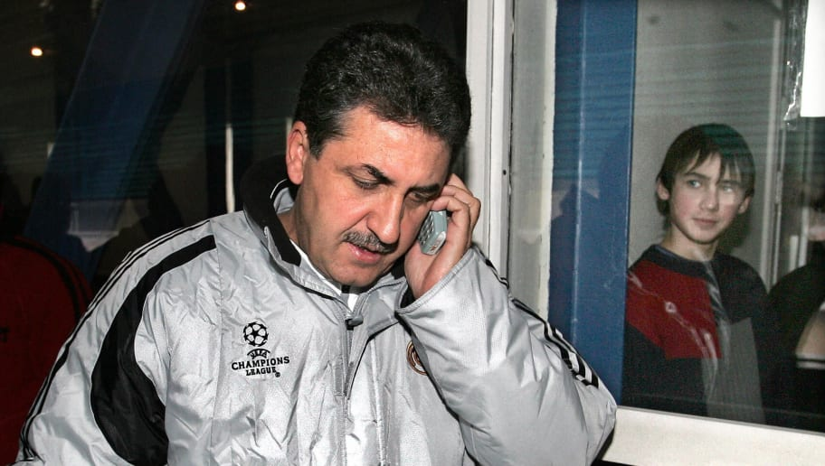 KIEV, UKRAINE:  Real Madrid head coach Garcia Remon speakes on his mobile phone as a boy behind a window looks at him after a press conference in Kiev, 02 November 2004, a day before the UEFA Champions League football match against Dinamo Kiev. AFP PHOTO / YURI KADOBNOV  (Photo credit should read YURI KADOBNOV/AFP/Getty Images)