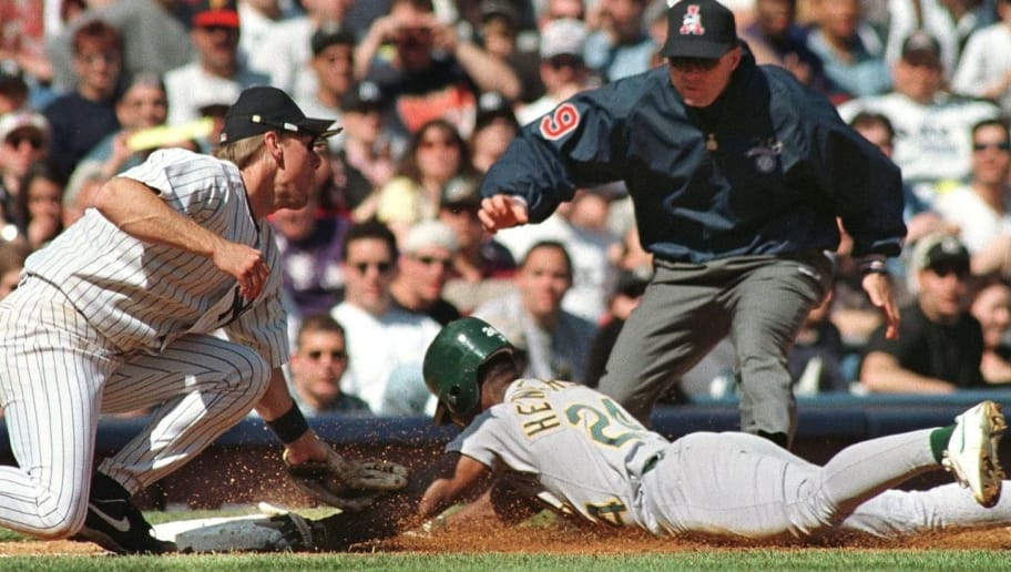NEW YORK, UNITED STATES:  Rickey Henderson of the Oakland Athletics (C) is caught stealing third base as Scott Brosius of the New York Yankees (L) makes the tag and umpire Ed Hickox (R) makes the call in the fifth inning of their game 12 April at Yankee Stadium in New York.   AFP PHOTO/Stan HONDA (Photo credit should read STAN HONDA/AFP/Getty Images)