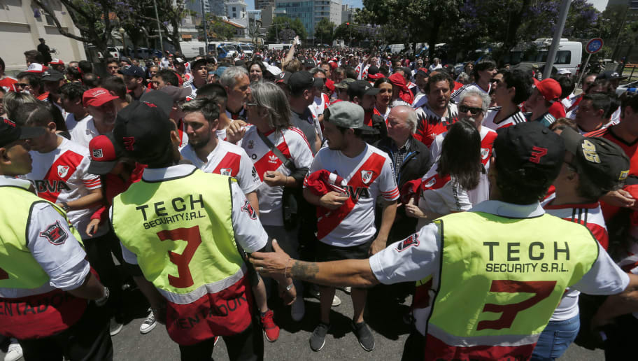 BUENOS AIRES, ARGENTINA - NOVEMBER 25: Police officers look at River fans on their way to the stadium prior the second leg of the final of Copa CONMEBOL Libertadores 2018 between River Plate and Boca Juniors at Estadio Monumental Antonio Vespucio Liberti on November 25, 2018 in Buenos Aires, Argentina. The match was suspended yesterday due to the attacks suffered by players of Boca Juniors on their arrival to the satdium and was rescheduled for today. (Photo by Marcelo Hernandez/Getty Images)