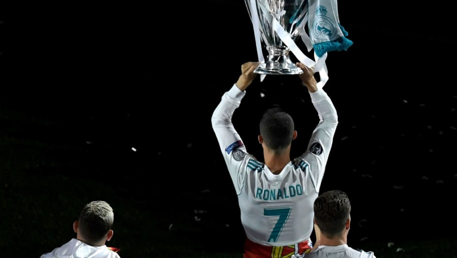 Real Madrid's Portuguese forward Cristiano Ronaldo holds the trophy at the Santiago Bernabeu stadium in Madrid on May 27, 2018 during a victory ceremony after Real Madrid won its third Champions League title in a row in Kiev. (Photo by GABRIEL BOUYS / AFP)        (Photo credit should read GABRIEL BOUYS/AFP/Getty Images)