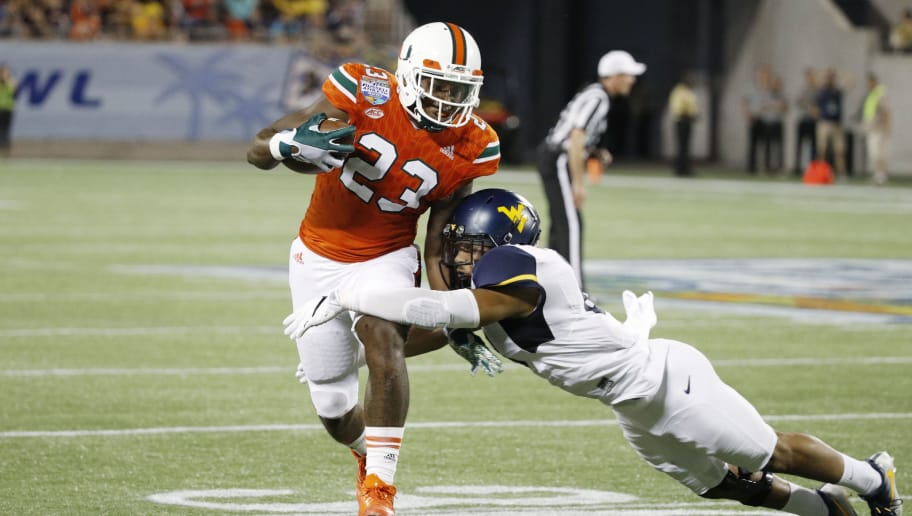 ORLANDO, FL - DECEMBER 28: Chris Herndon IV #23 of the Miami Hurricanes gets tackled after a reception against the West Virginia Mountaineers in the second half of the Russell Athletic Bowl at Camping World Stadium on December 28, 2016 in Orlando, Florida. Miami defeated West Virginia 31-14. (Photo by Joe Robbins/Getty Images)