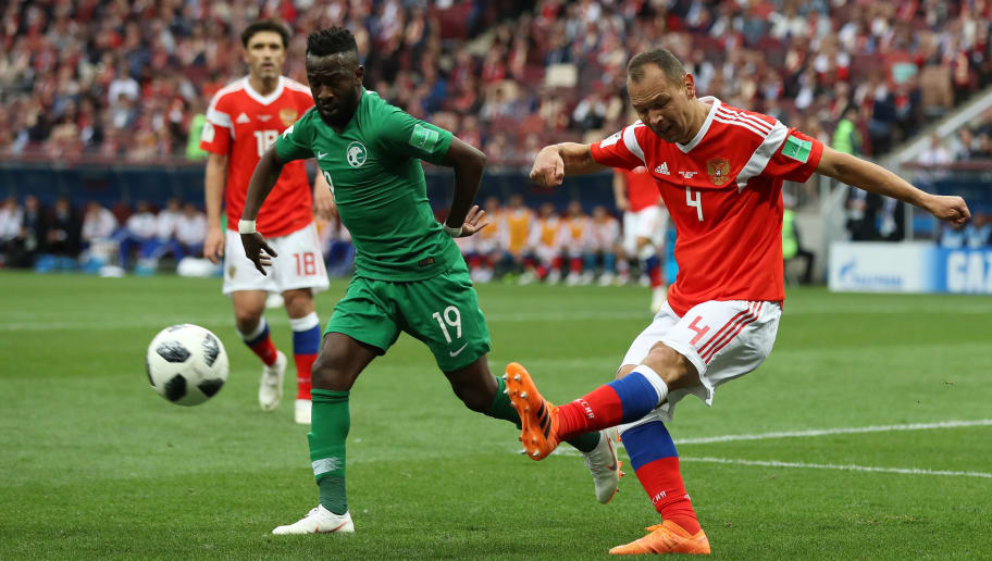 MOSCOW, RUSSIA - JUNE 14:  Sergey Ignashevich of Russia is challenged by Fahad Almuwallad of Saudi Arabia during the 2018 FIFA World Cup Russia Group A match between Russia and Saudi Arabia at Luzhniki Stadium on June 14, 2018 in Moscow, Russia.  (Photo by Ryan Pierse/Getty Images)