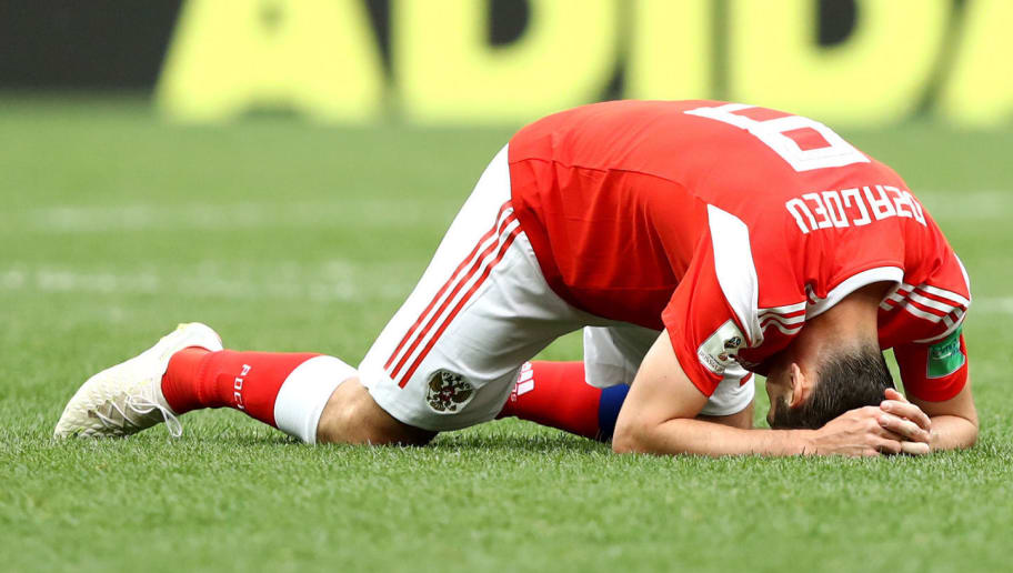 MOSCOW, RUSSIA - JUNE 14:  Alan Dzagoev of Russia goes down injured during the 2018 FIFA World Cup Russia Group A match between Russia and Saudi Arabia at Luzhniki Stadium on June 14, 2018 in Moscow, Russia.  (Photo by Ryan Pierse/Getty Images)