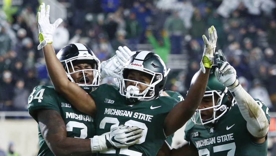 EAST LANSING, MI - NOVEMBER 24:  Cornerback Josiah Scott #22 celebrates with linebacker Antjuan Simmons #34 and safety Khari Willis #27 of the Michigan State Spartans after intercepting a pass by quarterback Giovanni Rescigno #17 of the Rutgers Scarlet Knights during the fourth quarter at Spartan Stadium on November 24, 2018 in East Lansing, Michigan. Michigan State defeated Rutgers 14-10.  (Photo by Duane Burleson/Getty Images)