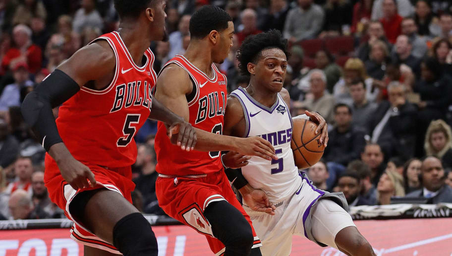 CHICAGO, ILLINOIS - DECEMBER 10: De'Aaron Fox #5 of the Sacramento Kings drives against Bobby Portis #5 and Shaquille Harrison #3 of the Chicago Bulls on his way to a game-high 25 points at the United Center on December 10, 2018 in Chicago, Illinois. The Kings defeated the Bulls 108-89. NOTE TO USER: User expressly acknowledges and agrees that, by downloading and or using this photograph, User is consenting to the terms and conditions of the Getty Images License Agreement.  (Photo by Jonathan Daniel/Getty Images)